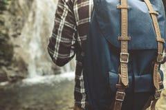 Onherkenbare Mensenreiziger met Rugzaktribunes met Zijn Rug op de Reistrek Waterval van de Achtergrondclose-up Wandelingsreis Con Royalty-vrije Stock Afbeeldingen