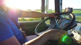 Onherkenbare mensenzitting achter wiel van zijn vrachtwagen en het drijven door platteland bij zonsondergang Bestuurder die zijn  stock videobeelden