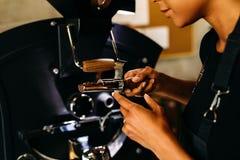 Onherkenbare vrouw die een kwaliteit van geroosterde koffie controleren Royalty-vrije Stock Fotografie