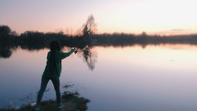 Onherkenbare vrouw die op de kust van de vijver bij zonsondergang in de avond vissen Achter mening stock video