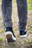 Onherkenbare vrouw die in rubberschoenen op het voetpad, achter verticale mening stappen, Stock Afbeeldingen