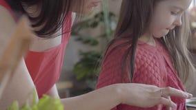 Onherkenbare vrouw en haar weinig dochterspel op tablet dichte omhooggaand Moeder die het scherm van dochter scrollen stock videobeelden