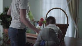 Onherkenbare vrouw enkel terug van de winkel De moeder trekt zich van de de het mandmelk, brood, greens en tulpen terug, toen stock videobeelden