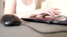 Onherkenbare vrouw gebruikend een muis en typend iets op laptop toetsenbord, ondiepe nadruk stock video