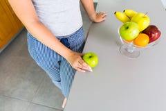Onherkenbare vrouw in keuken met vruchten Stock Afbeeldingen