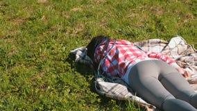 Onherkenbare vrouw met blauwe Afrikaanse vlechten die op het gazon in het Park slapen stock footage
