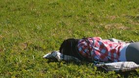 Onherkenbare vrouw met blauwe Afrikaanse vlechten die op het gazon in het Park slapen stock video