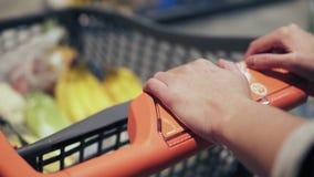 Onherkenbare vrouwelijke handen die boodschappenwagentje in kruidenierswinkelopslag duwen stock video