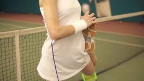 Onherkenbare vrouwelijke tennisspeler in sexy witte sportkleding die uit beenspieren uitrekken alvorens te beginnen te spelen stock footage