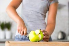 Onherkenbare vrouwen snijdende appel in keuken Stock Foto's