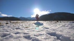 Onherkenbare wandelaar die met stok omhoog op sneeuwheuvel op gebied bij zonnige dag beklimmen Jonge mannelijke toerist die op sn stock video