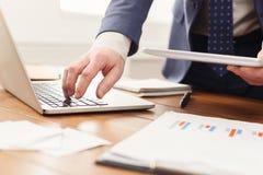 Onherkenbare zakenman die laptop en tablet gebruiken Stock Afbeeldingen