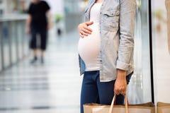 Onherkenbare zwangere vrouw wat betreft haar buik, die zakken houden, royalty-vrije stock fotografie