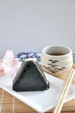 Onigiri日本食物用在背景的茶 图库摄影