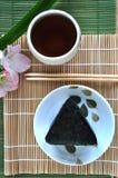 Onigiri顶视图用在竹席子的茶 免版税库存照片