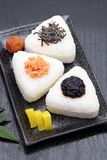Onigiri. Rice triangle with takuan and umeboshi