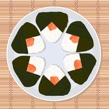 Onigiri japanese rice ball filled with salmon. Lunch texture. Japanese cuisine. Lunch Illustration. Asian snack plate on the japanese bamboo mat Stock Photography
