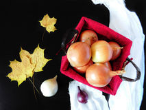 Onion in a basket. Surrounded by autumn leaves stock photo