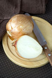 Onion on board with knife Royalty Free Stock Photo