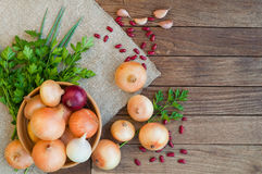 Onion in bowl on sacking and  wooden background. Vegetables. Onion in bowl on sacking and  wooden background Stock Image