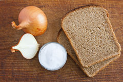 Onion, bread and salt. On a wooden Board Royalty Free Stock Photo