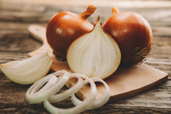 Onion bulb on chopping board with onion slices Stock Images