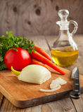 Onion, carrots and fresh parsley on a chopping board. Stock Images