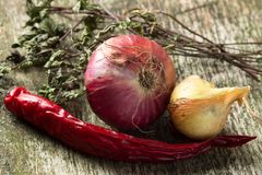 Onion and Chilli Pepper with herbs on old wood board Stock Photo