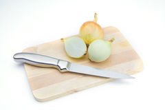 Onion on chopping board Stock Images