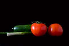 Onion, cucumber and tomatoes. Composition of fresh vegetables: green onion, cucumber and two tomatoes Royalty Free Stock Photo