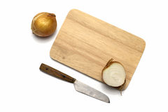 Onion on cutting board with knife Stock Images