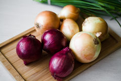 Onion on the cutting wood board. Many onion on the cutting wood trencher royalty free stock photography