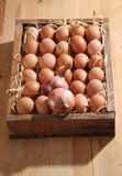 Onion eggs. Bunch of fresh brown eggs and some straw in a wooden crate Stock Image
