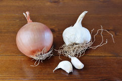 Onion and garlic. An onion, a bulb and two clove of garlic on a wooden table stock photography