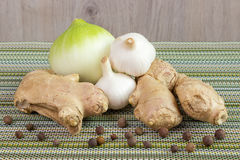 Onion, garlic bulb and ginger. On the table Royalty Free Stock Image