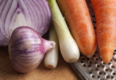 Onion, garlic carrots and old grater. Close up Stock Image