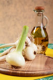 Onion and garlic with an olive oil bottle Stock Images