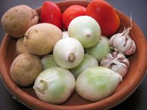 Onion Garlic Potato Tomato Vegetables. Closeup of fresh organic vegetables in a clay dish. Raw veggies  in a bowl on a wooden table. Background royalty free stock photography