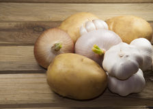 Onion, garlic and potatoes. On wooden place Stock Photography