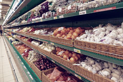 Onion and garlic on supermarket shelf, no trademarks. Toned image Royalty Free Stock Images