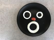 Onion and grape tomato looks like human face. Three pieces of onion and half of red grape tomato displayed on black plate looks like human face putted on gray Royalty Free Stock Photos