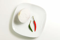 Onion with green and red hot peppers on a plate Stock Photo