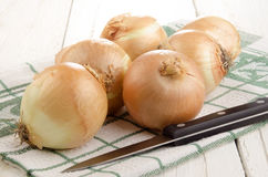 Onion and kitchen knife on a kitchen towel Royalty Free Stock Image