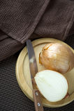 Onion with knife on board Stock Photos