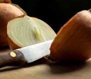 Onion and knife on wooden board Royalty Free Stock Photography