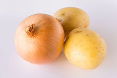 Onion and potatoes on white background. An onion and two raw potatoes arranged on a white background Royalty Free Stock Photos