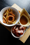 Onion ring, bacon poutine. Deliciously unhealthy onion ring poutine with bacon on wooden cutting board Stock Photo