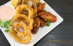 Onion rings and barbecue wings Royalty Free Stock Photo