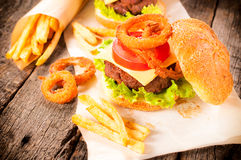 Onion rings and burger. Onion rings,beef burger and french fries on the table.Selective focus on the onion ring and burger Royalty Free Stock Images