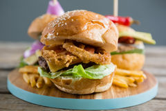 Onion rings in burger. Close up of onion rings in burger on cutting board Royalty Free Stock Photo